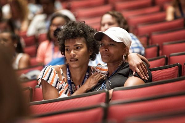 Mother and daughter sit arm in arm while sitting in a Big Blue Nation Orientation session.