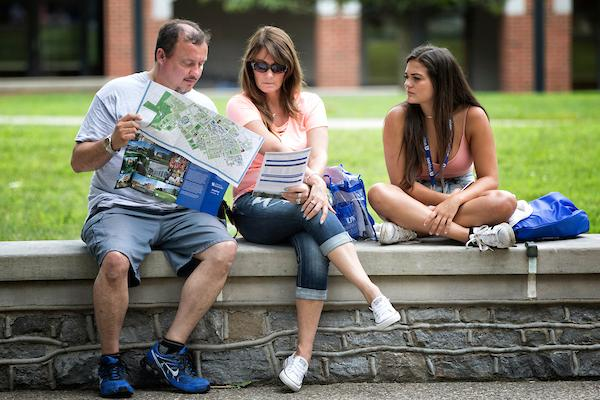 Student and parents sitting on short campus wall looking at a map