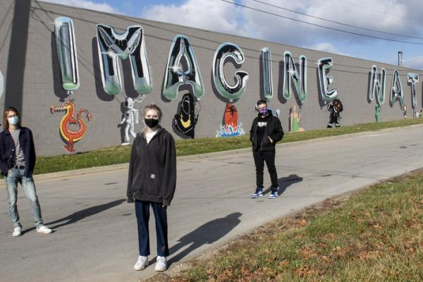 Photo of students in front of mural they created called Imagine Nation