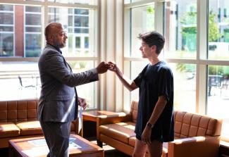 A student fist bumps their advisor in the lobby of the Lewis Honors College.