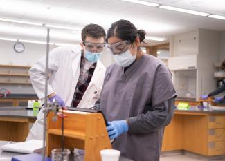 A student and professor work together in a chemistry lab.