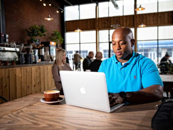 A black male student works on a laptop while sitting in a coffeeshop.