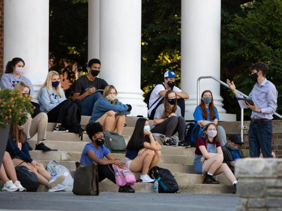 A class meets outside on the steps of Memorial Hall.